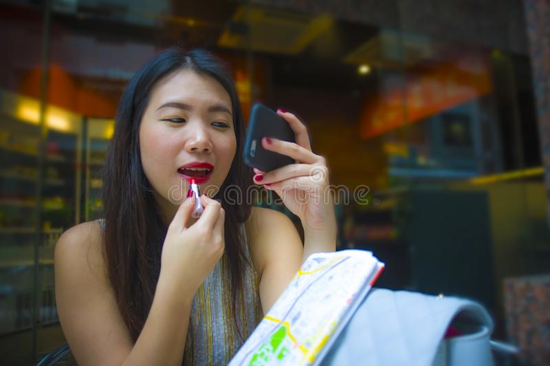 Young happy and attractive Asian Korean tourist woman sitting at city coffee shop using lipstick makeup and mobile phone mirror wa. Lifestyle portrait of young stock photo