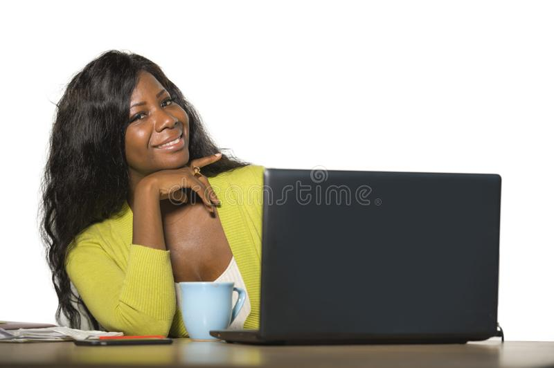 Young happy and attractive black African American business woman smiling cheerful and confident working at office computer desk re. Laxed in successful stock photography