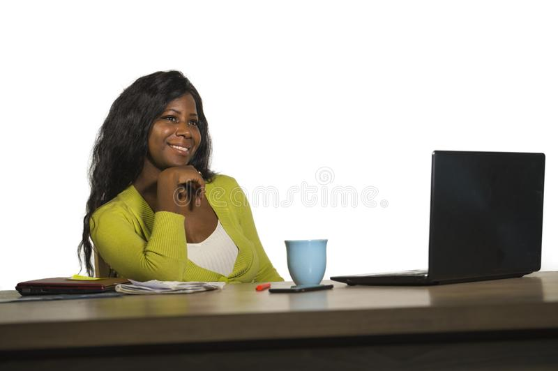 Young happy and attractive black African American business woman smiling cheerful and confident working at office computer desk re. Laxed in successful stock image