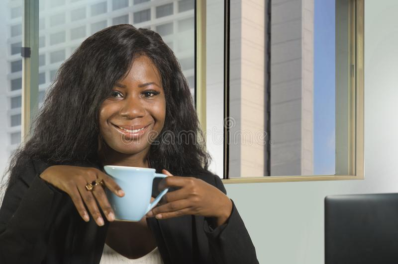 Young happy and attractive black African American businesswoman working confident at computer desk drinking coffee smiling satisfi. Office corporate portrait of royalty free stock image