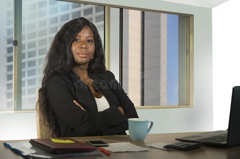 Young happy and attractive black African American businesswoman working confident at computer desk smiling satisfied in financial. Office corporate portrait of stock image