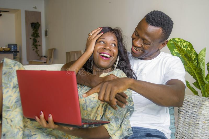 Young happy and attractive black African American couple together at home sofa couch networking with laptop computer banking. Online or internet shop relaxed stock photography