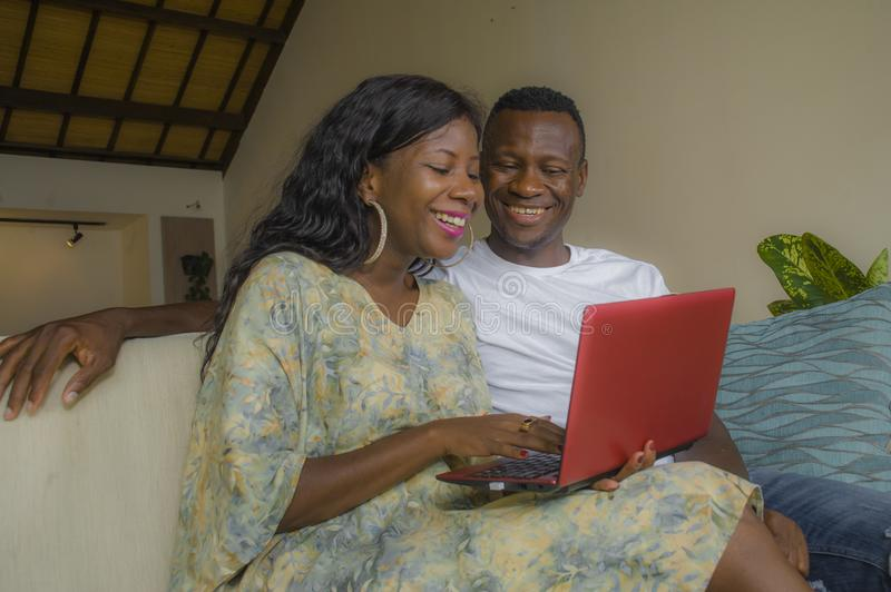Young happy and attractive black African American couple together at home sofa couch networking with laptop computer banking. Online or internet shop relaxed royalty free stock photography