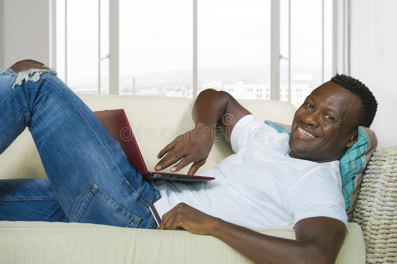 Young happy and attractive black African American man using credit card and laptop computer relaxed and cheerful at living room. Lifestyle portrait of young stock images