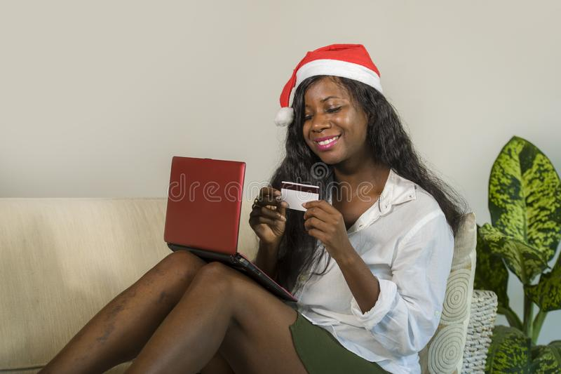 Young happy and attractive black African American woman in Santa Claus hat holding credit card buying Christmas present and gift o stock image