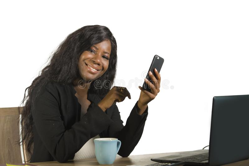 Young happy and attractive black afro American business woman working at office computer desk smiling successful using mobile phon. E as efficient and royalty free stock photos