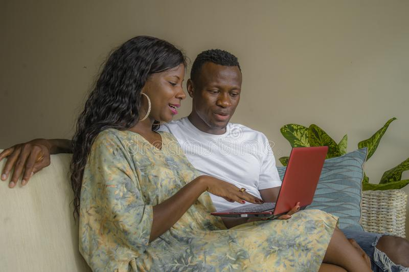 Young happy and attractive black afro American couple together at home sofa couch networking with laptop computer banking online. Or internet shop relaxed and royalty free stock photos