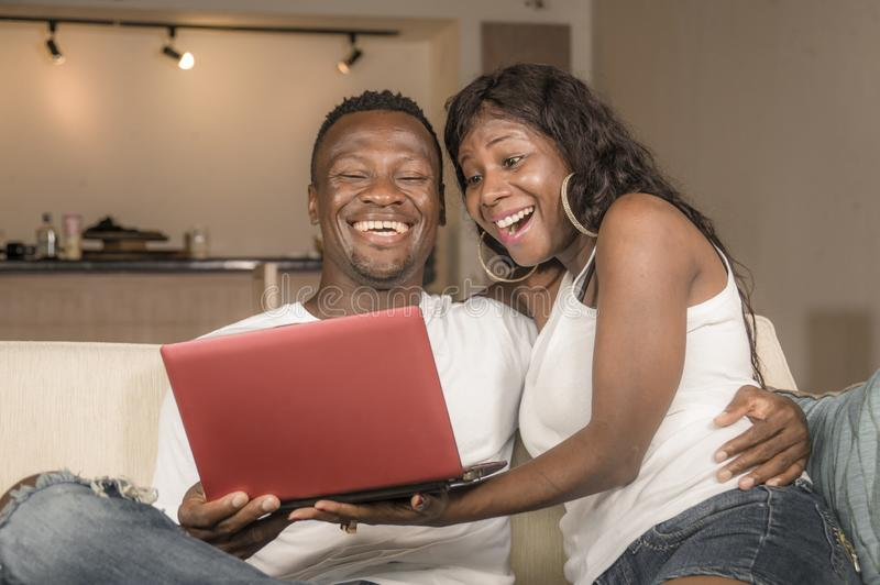 Young happy and attractive black afro American couple together at home sofa couch networking with laptop computer banking online. Or internet shop relaxed and royalty free stock images