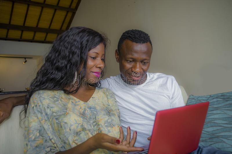 Young happy and attractive black afro American couple together at home sofa couch networking with laptop computer banking online. Or internet shop relaxed and stock image