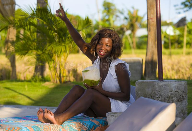 Young happy and attractive black afro American woman lying on pool hammock at tropical beach resort chilling relaxed drinking stock photography