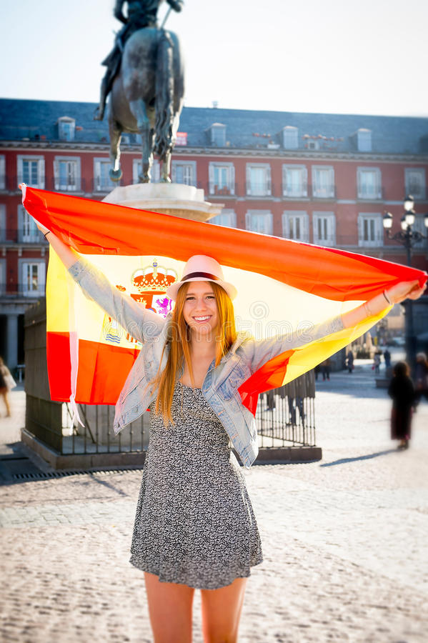 Young happy attractive exchange student girl having fun in town visiting Madrid city showing Spain flag royalty free stock photography