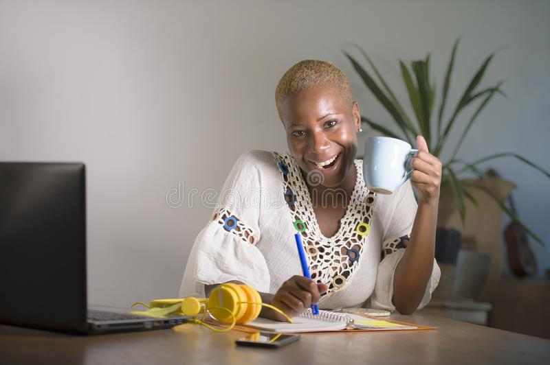 Young happy and attractive hipster black afro American woman drinking tea or coffee at home office working cheerful with laptop co royalty free stock image