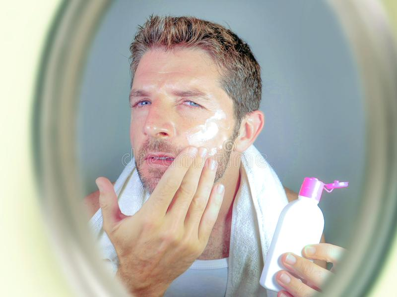 Young happy and attractive man applying moisturizer lotion or anti aging beauty cream smiling confident and conscious looking at b. Athroom mirror in skin care stock images