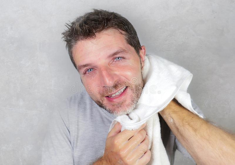 Young happy and attractive man using towel drying face after washing looking at the bathroom mirror smiling cheerful and positive stock photos