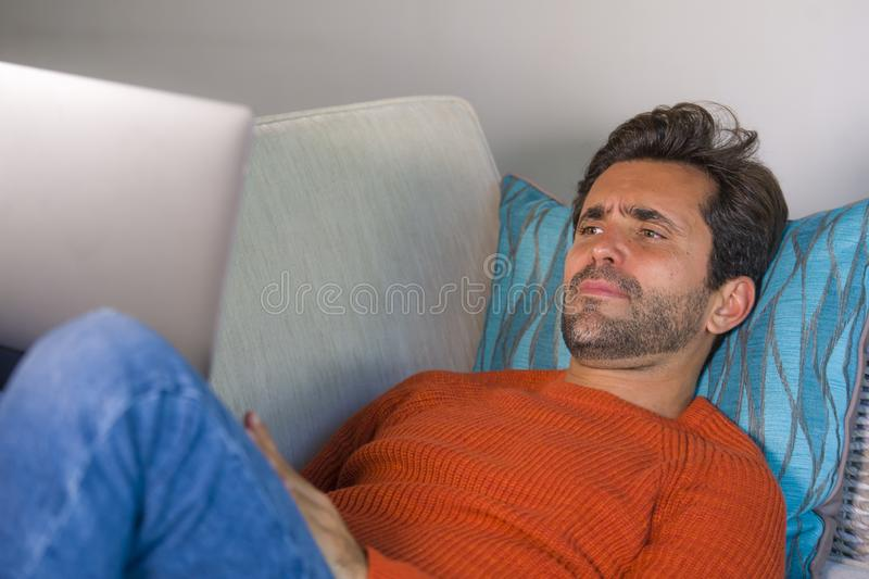 Young happy and attractive man working relaxed with laptop computer at modern apartment living room lying at sofa couch typing and. Networking in entrepreneur royalty free stock image