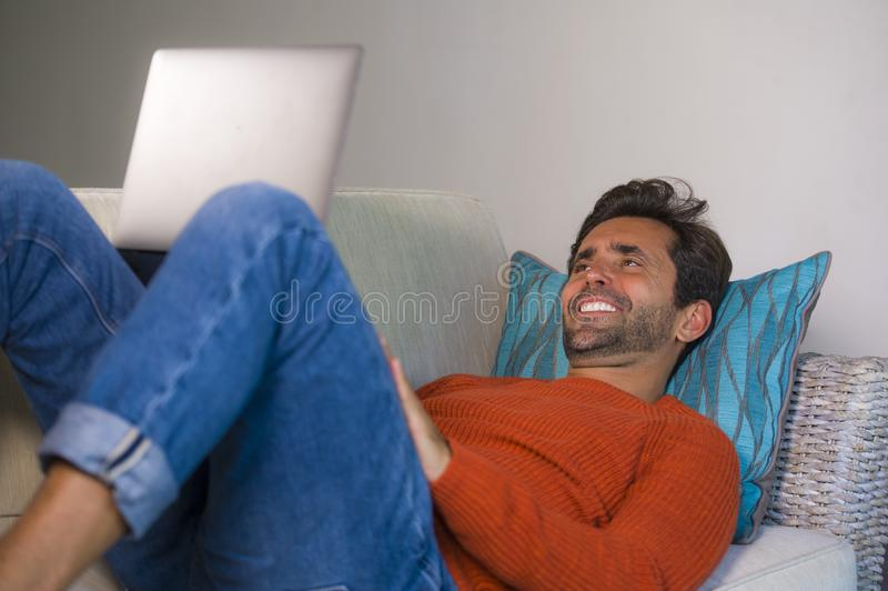 Young happy and attractive man working relaxed with laptop computer at modern apartment living room lying at sofa couch typing and. Networking in entrepreneur stock images