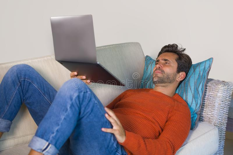 Young happy and attractive man working relaxed with laptop computer at modern apartment living room lying at sofa couch typing and. Networking in entrepreneur stock image