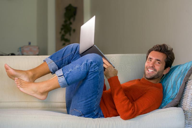 Young happy and attractive man working relaxed with laptop computer at modern apartment living room lying at sofa couch typing and. Networking in entrepreneur royalty free stock photography