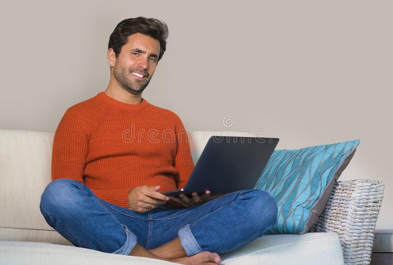 Young happy and attractive man working relaxed with laptop computer at modern apartment living room sitting at sofa couch typing a. Nd networking in entrepreneur stock photo