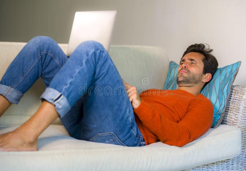 Young happy and attractive man working relaxed with laptop computer at modern apartment living room sitting at sofa couch typing a. Nd networking in entrepreneur stock photos