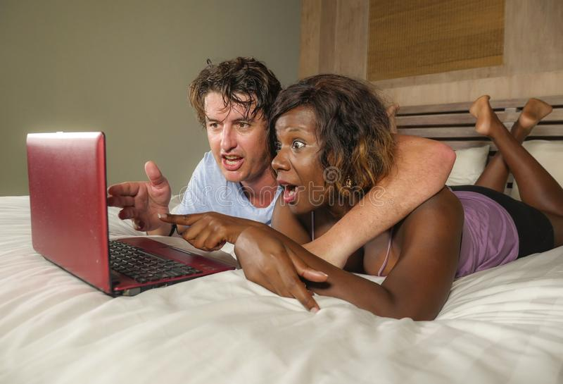 Young happy and attractive multiracial couple with beautiful black African American ethnicity woman and white man lying relaxed on. Bed shopping online using stock images