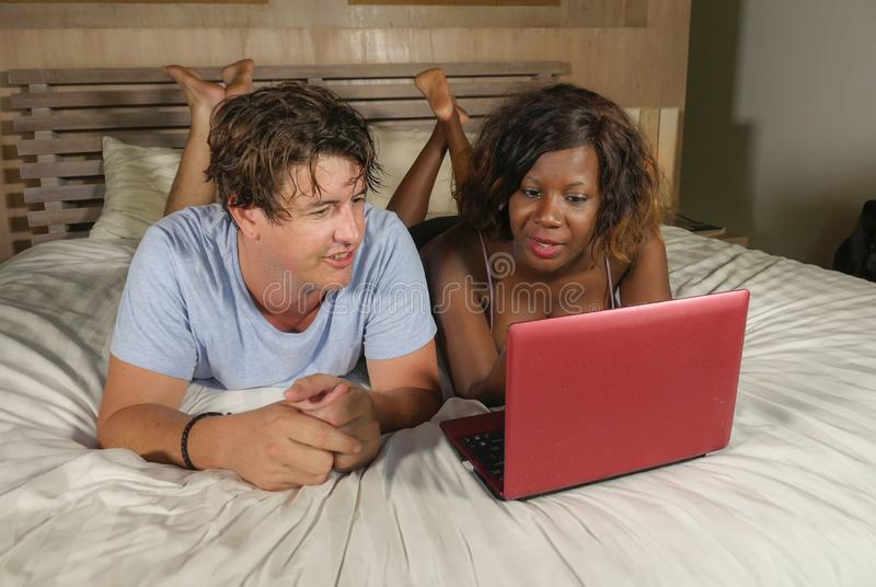 Young happy and attractive multiracial couple with beautiful black African American ethnicity woman and white man lying relaxed on. Bed shopping online using royalty free stock photography