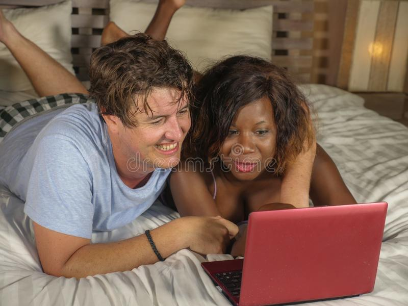 Young happy and attractive multiracial couple with beautiful black African American ethnicity woman and white man lying relaxed on. Bed shopping online using stock image
