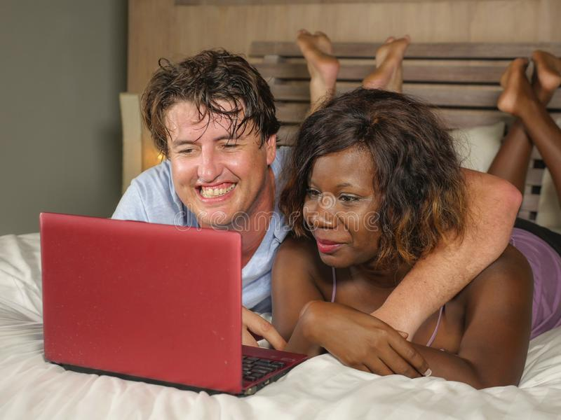 Young happy and attractive multiracial couple with beautiful black African American ethnicity woman and white man lying relaxed on. Bed shopping online using stock photos