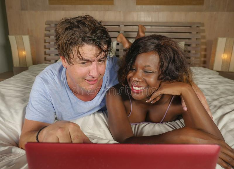Young happy and attractive multiracial couple with beautiful black afro American ethnicity woman and white man lying relaxed on. Young happy and attractive stock photo