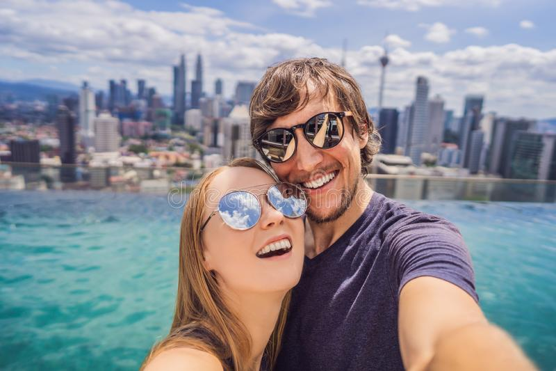 Young happy and attractive playful couple taking selfie picture together at luxury urban hotel infinity pool and royalty free stock photos