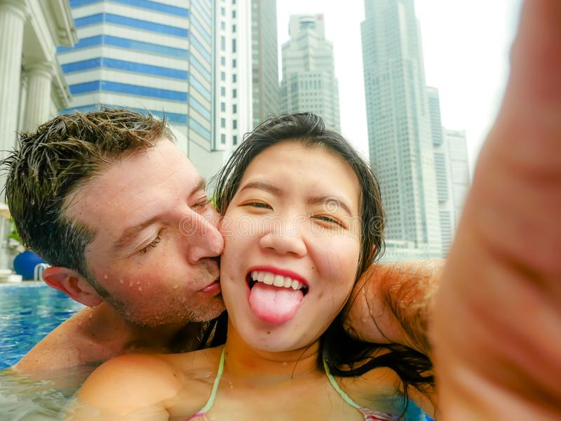 Young happy and attractive playful couple taking selfie picture together with mobile phone at luxury urban hotel kissing at infini royalty free stock image