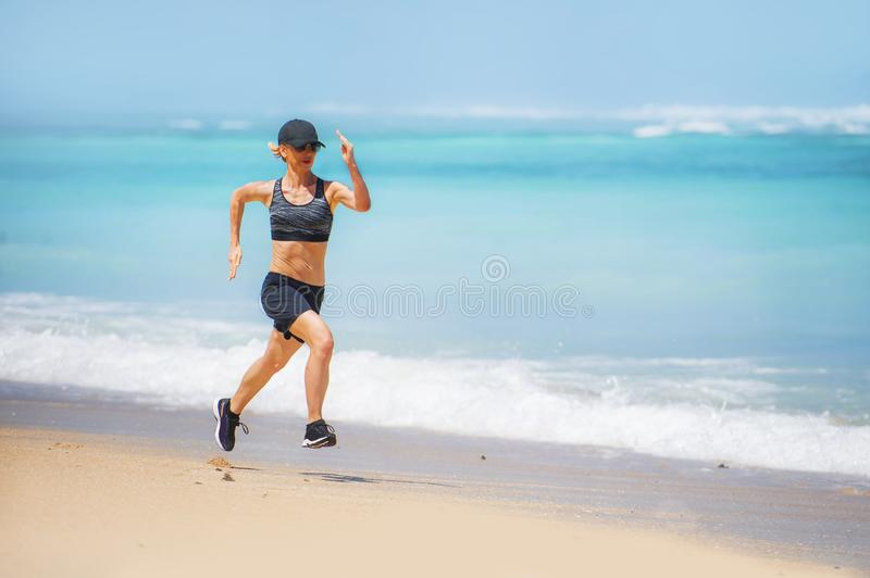 Young happy and attractive sport runner woman doing running workout sprinting on tropical paradise beach showing fit and athletic royalty free stock image