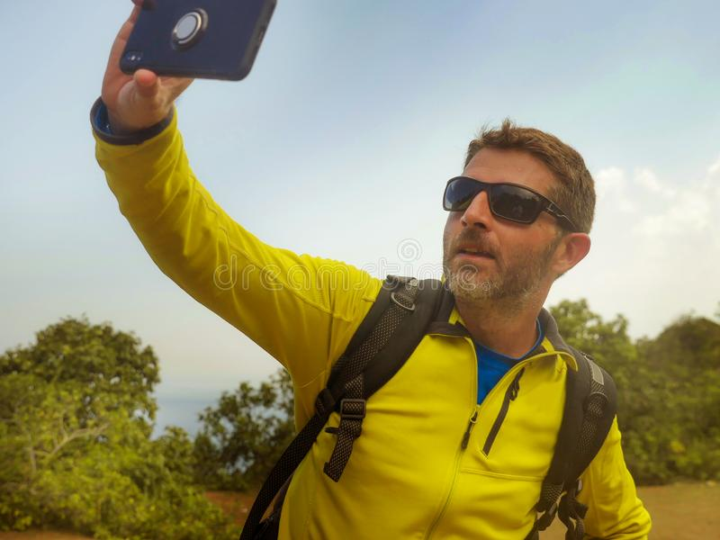 Young happy and attractive sporty hiker man with trekking backpack hiking at mountain taking selfie enjoying travel getaway stock photo