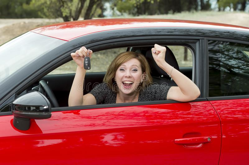 Attractive woman smiling proud sitting at driver seat holding and showing car key in new automobile buying and renting stock photos