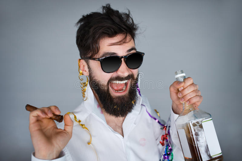 Young happy bearded man having a drink on grey background royalty free stock image