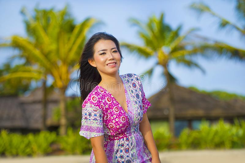 Young happy beautiful Asian Chinese tourist woman smiling relaxed wearing sweet dress walking at beach tropical resort on holidays royalty free stock image