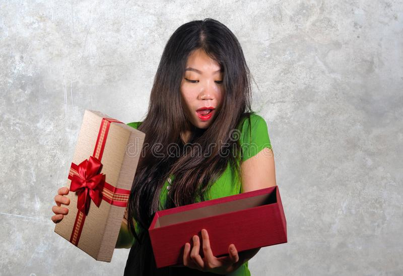 Young happy and beautiful Asian Chinese woman holding gift box receiving birthday or Christmas present opening the parcel excited. Isolated grey background stock images