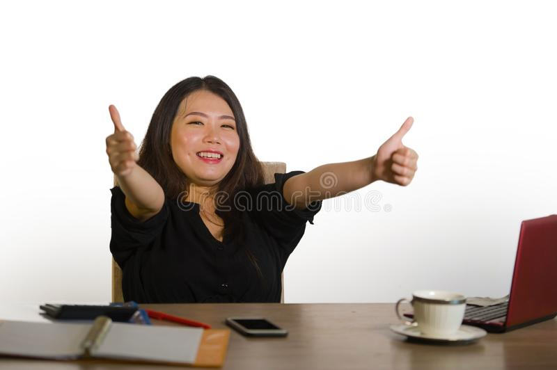 Young happy and beautiful Asian Korean business woman celebrating successful job achievement excited giving thumb up working at of royalty free stock photos