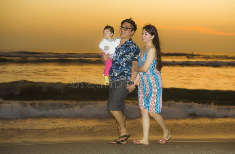 Young happy and beautiful Asian Korean couple holding baby girl daughter walking on sunset beach enjoying together romantic summer royalty free stock photos
