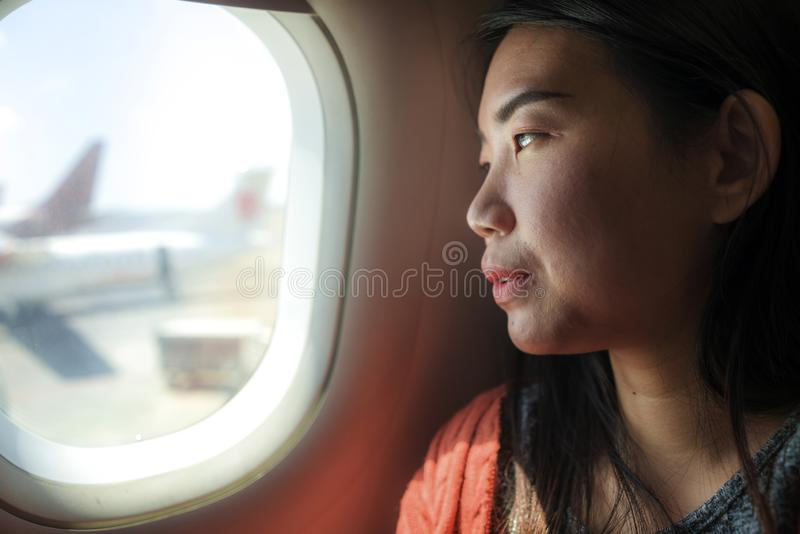 Young happy and beautiful Asian Korean tourist woman smiling excited sitting in airplane by the window arriving destination in stock image