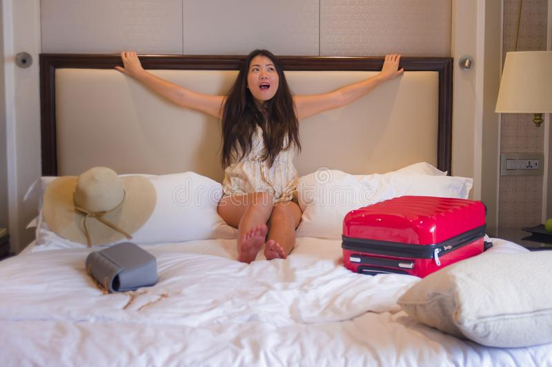 Young happy and beautiful Asian Korean tourist woman with travel suitcase just arrived at five star hotel room sitting on bed star stock photography