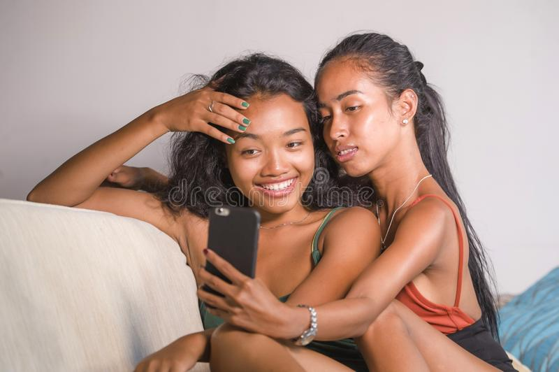 Young happy and beautiful Asian sisters or girlfriends couple smiling cheerful taking selfie photo with mobile phone at home couch. Playful laughing together in stock photo