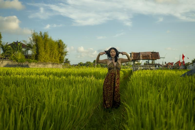 Young happy and beautiful Asian woman enjoying nature at rice field. sweet Korean girl exploring countryside during holiday travel royalty free stock photo