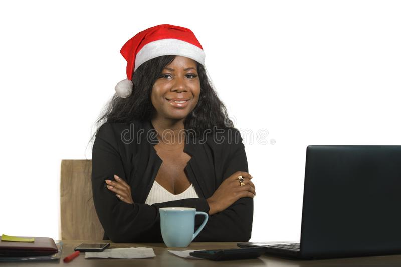 Young happy and beautiful black afro American business woman in Santa Christmas hat working at office computer desk smiling succes. Sful posing corporate royalty free stock image