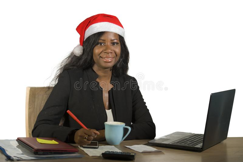 Young happy and beautiful black afro American business woman in Santa Christmas hat working at office computer desk smiling succes. Sful posing corporate royalty free stock photography
