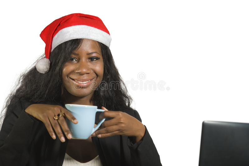 Young happy and beautiful black afro American business woman in Santa Christmas hat working at office computer desk smiling succes. Sful posing corporate stock photos