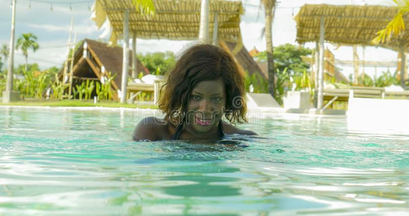 Happy and beautiful black afro American woman in bikini having fun at tropical beach resort swimming pool relaxed and playful. Young happy and beautiful black royalty free stock image
