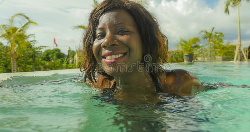 Happy and beautiful black afro American woman in bikini having fun at tropical beach resort swimming pool relaxed and playful. Young happy and beautiful black royalty free stock photography