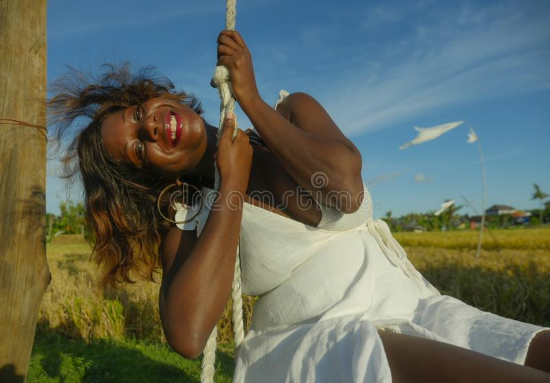Young happy and beautiful black afro American woman in Summer dress playing outdoors on swing smiling cheerful and relaxed having. Fun swinging in tropical stock images