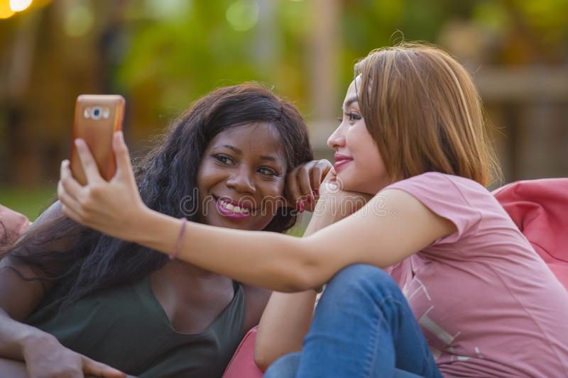 Young happy and beautiful black afro American woman enjoying holidays at tropical resort with Asian girlfriend taking selfie. Young happy and beautiful black stock photos